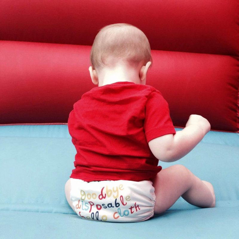 "Toddler sitting on a bouncy castle wearing a reusable nappies that says ""Goodbye disposable, Hello Cloth"""
