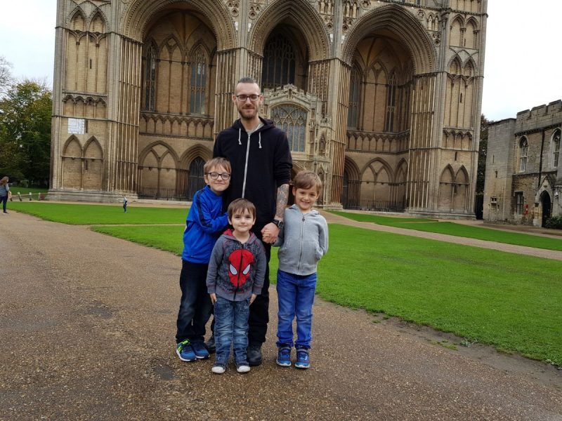 Family standing together in front of Peterborough Cathedral